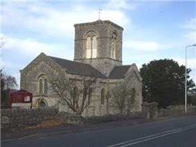 Stone building with arched windows and central square tower.In the foreground are trees and a road.