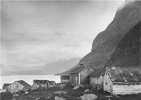 Small wooden huts with pitched roofs, some with no windows, huddle under a steep cliff on a fjord.