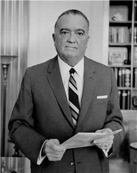A portrait of a man, standing, holding papers