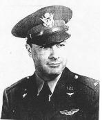 Head and shoulders of a man wearing a peaked cap and a military jacket with a winged pin on the left breast and pins on the lapels.