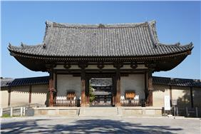Wooden gate with white walls and a hip-and-gable roof.
