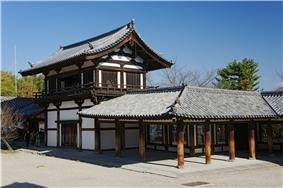 Two-storied wooden building with white walls and an attached open veranda with handrail on the upper floor.