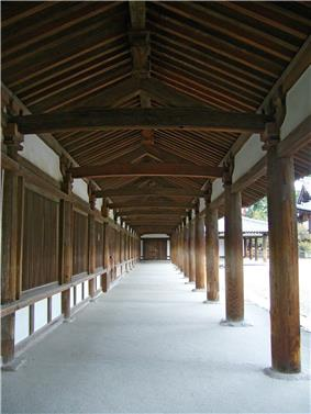 A semi-open wooden corridor with white walls.