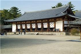 Wide and low wooden building with white walls and a hip-and gable roof.