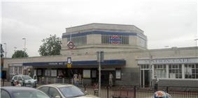 A light grey building with a long, rectangular, dark blue sign reading