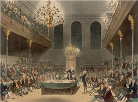 View of a large room, showing the Speaker of the House sitting at the end. Down each side of the room, MPs are sitting – one MP is standing on the right, giving a speech. Balconies are on either side, with spectators visible.