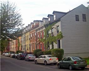 A row of attached houses along a street, seen from further down along the opposite side, on the right of the image. All are of brick, in various colors, three stories high, with gabled roofs and gabled dormer windows. There are tall trees on the right and cars parked along the same side of the street as the houses.