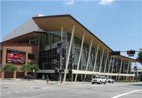 Concrete auditorium fronted by a large glass atrium over which is a slightly curved roof supported by narrow, angled poles.