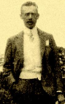 Photo of Burnham's brother Mather Howard Burnham.  Howard is wearing a suit and tie and standing with his right hand in his pocket.