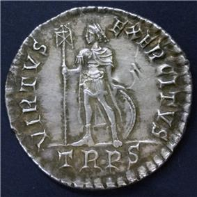 Silver coin showing a man standing with a standard and a round shield behind his legs. There is writing round the edge including