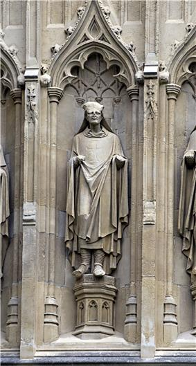 Stone statue of a robed man set in a niche. The top half of the head of the statue is missing.