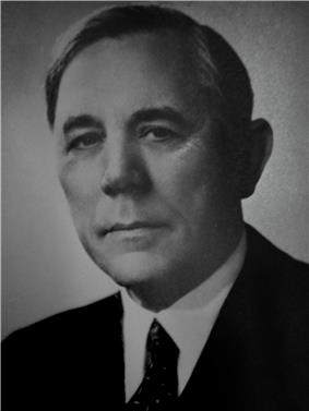A black-and-white bust portrait of a distinguished man in a suit.