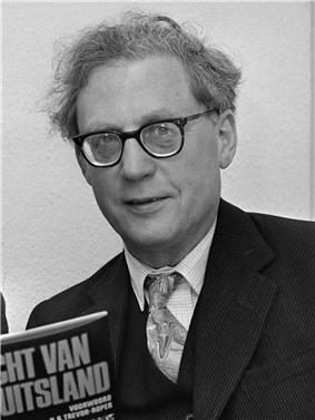Cropped black and white photograph of Trevor-Roper being given a book