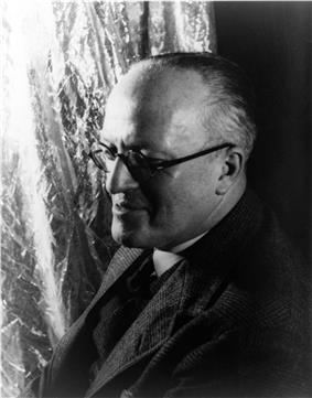 profile head and shoulders of balding, clean-shaven middle-aged man in mid-20th century clothes
