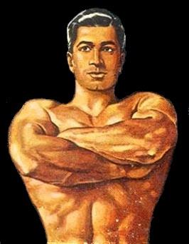 Muscular man with slicked back hair, seen from the waist up, shirtless with arms folder.