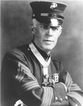 Top half of man in formal 1900s military dress, wearing a star-shaped medal on a ribbon around his neck.