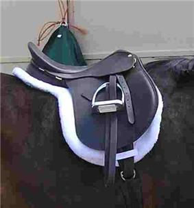 An English saddle set on top of a white pad that has the same shape as the saddle