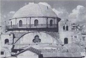 A large domed roof sits upon a bricked parapet, which includes arched windows, three of which are visible. The base of the parapet is surrounded by a narrow veranda, which is fenced with decorative metal grating. Below this, a central clover shaped window lies at the top of an arched wall. Two supporting towers stand on the left and right, each containing an arched window. The right tower, capped with a small dome, is a storey higher, reaching to the top of the bricked parapet, which supports the domed roof.