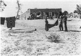 Photo of Navajo woman and two white men holding a blanket in front of a building