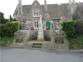 Stone cross, with red wreaths, separated from a building behind by metal railings.