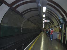 The interior of a building with a rounded ceiling and rounded walls with a railway track on the left and people standing on the right