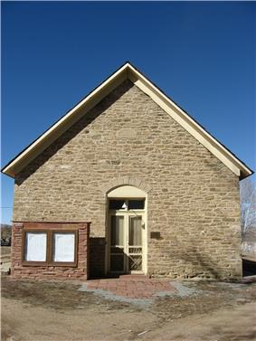A photograph of the front of a stone and redbrick church.