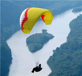 A person dangles below a red, yellow and white parasail, in the background is a lush forest with a large river and a tree-covered island.