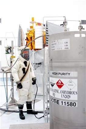 A suited worker looks over the hydrazine fuel supply to be loaded in MESSENGER.