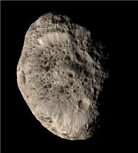 An irregularly shaped oblong body is illuminated from the left. The terminator is near the right limb. The body is elongated in the top-bottom direction. The surface is punctured by numerous impact craters, which make it look like a sponge or cheese.