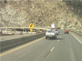 A sharp curve with a cut in the mountain visible to support the highway