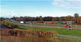 A divided highway going across a level landscape. On the right is a sign in English and French saying
