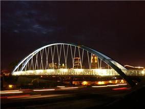 A large arched suspension bridge passes over a busy highway.  The nighttime skyline is seen through the cable supports.