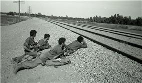 Israeli soldiers in prone position by a railway track