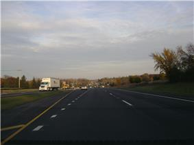 Eastbound IL120 west of Hunt Club Road. Road is divided highway with a grassy median and open areas on both sides with scattered trees.