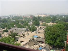A view down to the gabled roofs of single-story houses with some interspersed trees in the foreground. In the background, slightly obscured by smog, are taller, more modern buildings