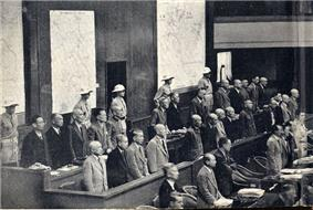 Three rows of benches with a dozen or so men standing behind each. Behind them stand five men in uniform.
