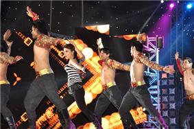 Priyanka Chopra dancing on stage with a group of men