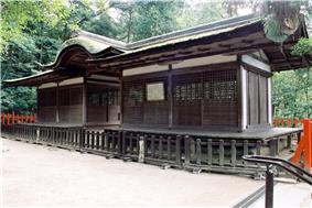 A wide wooden building with a passageway over which there is a Chinese style gable.