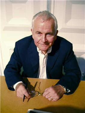 A color photograph of a man in a suit, sitting at a brown desk, holding a pair of glasses