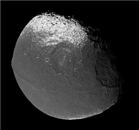 A walnut shaped body illuminated from the bottom-left. The terminator runs from the top to right along the top-right limb. An equatorial ridge runs from the left to right and is convex in the direction of the bottom-left. Above and below it there are dark areas. Above the upper dark area and below the lower one there are bright poles. There numerous craters. Three among them are very large: one sits on the limb at the right another is in the center above the ridge. The third is below the ridge near the left limb.