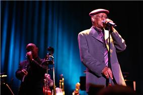 A man wearing a cap on his head, eyeglasses, and a suit, holding on to a microphone stand with both hands. To the left of him is a man also holding on to a microphone stand. In between them are various musical instruments.