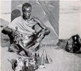 A black and white photo of an Igbo traditional spiritual practitioner known as dibia wearing a cloth alung round the should and sitting cross legged on an outside sand floor, tools of his practice are in front of him including what appear to be animal skins, a small carved image of Ikenga, and a bell. He has a white line of chalk over his eyes and is slightly bowing. In the background is a carved door with intricate lines carved into it, appearing to stick out the ground behind the man.