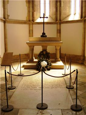 Photograph of a small chapel in which a roped-off inscribed stone slab is set into the floor and with a stone altar in the background on which are a wreath and a large metal cross