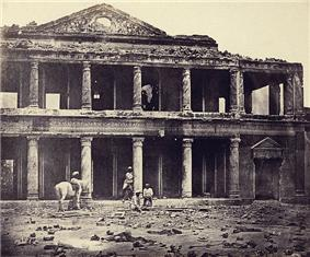 A photograph of the ruins of a palace with human skeletal remains in the foreground