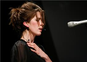 Imogen Heap face-on, on 12 October 2006 at the Carling Academy Birmingham, at a multi-tier set-up with keyboard atop which she's intently playing.  She has a headset microphone, then-characteristically back-combed hair, wears a sleeveless frilly pink bodice and is rear illuminated by two piercing green star-burst spotlights.