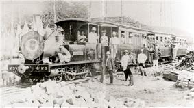 A black-and-white photo of a locomotive carrying and flanked by workers.