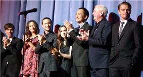 A man in a black suit, a woman in a pink dress, a man in a plaid suit, a woman in a black dress, a Japanese man in a black suit, and an old man in a blue suit clap their hands, while a man in a black suit stands. A microphone stand is in the foreground, and blue curtains are in the background.