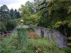 An overgrown area with a circular stone structure covered in ivy in the foreground and a wall with wide embrasures beyond. Tall trees, both conifers and deciduous overlook the scene.