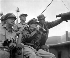 MacArthur is seated, wearing his field marshal's hat and a bomber jacket, and holding a pair of binoculars. Four other men also carrying binoculars stand behind him.