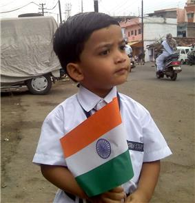 A child holding a small sized flag